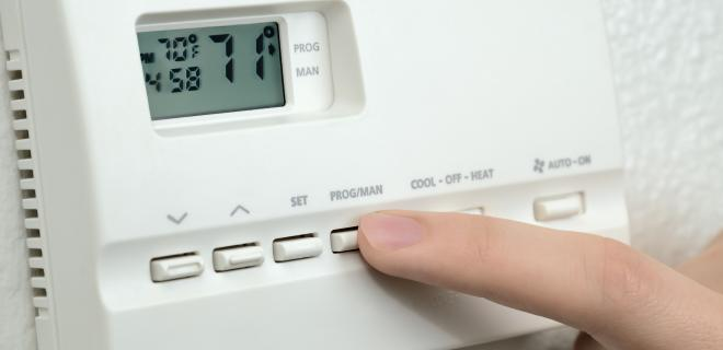 most efficient heating systems - finger pressing button on digital thermostat