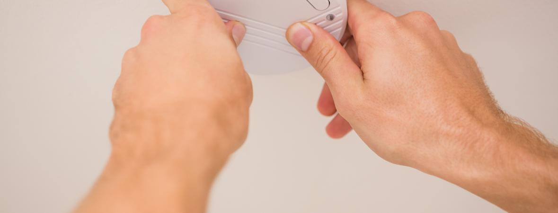 hands installing a carbon monoxide detector
