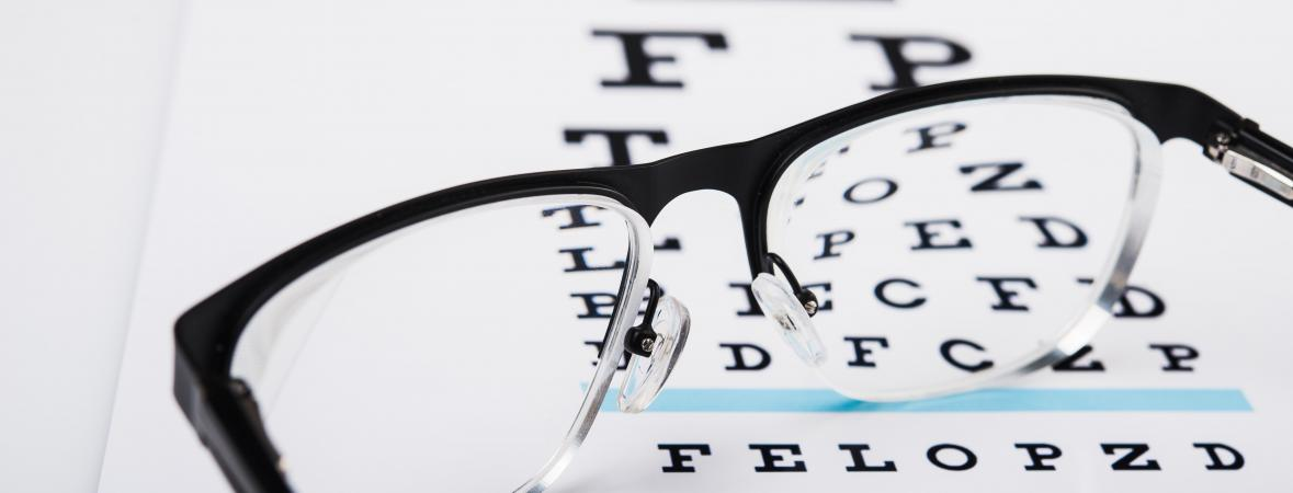 eye health and safety tips - reading glasses on an eye exam chart