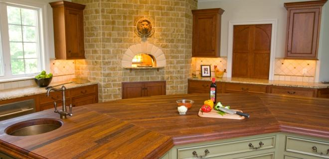 kitchen island with built-in sink, view of brick oven and countertops