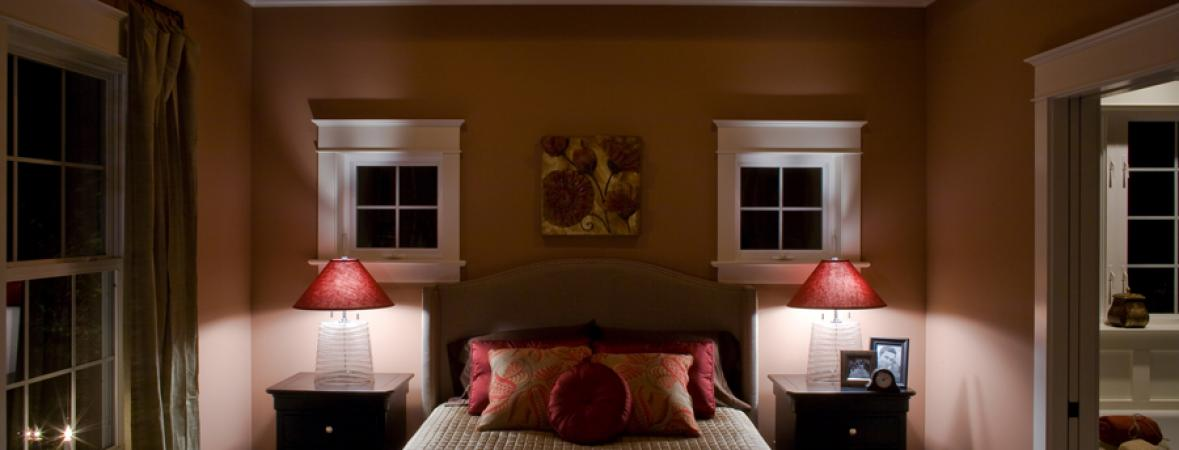 bedroom with recessed lights in the ceiling and two bedside tables with lamps