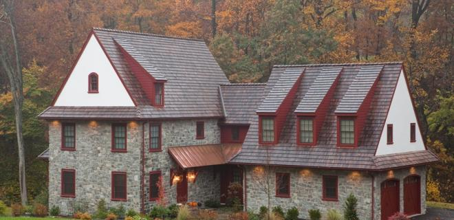 stone custom home with red roof