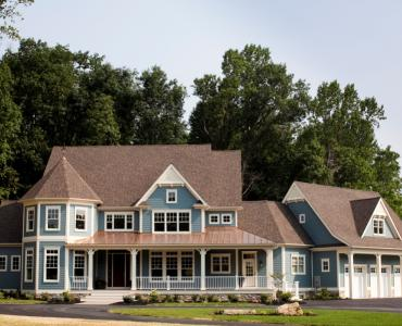blue custom home with wrap around porch and 3-car attached garage