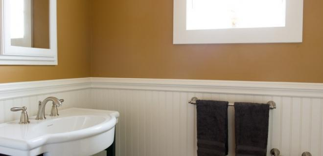 pedestal sink in bathroom with wainscoting trim