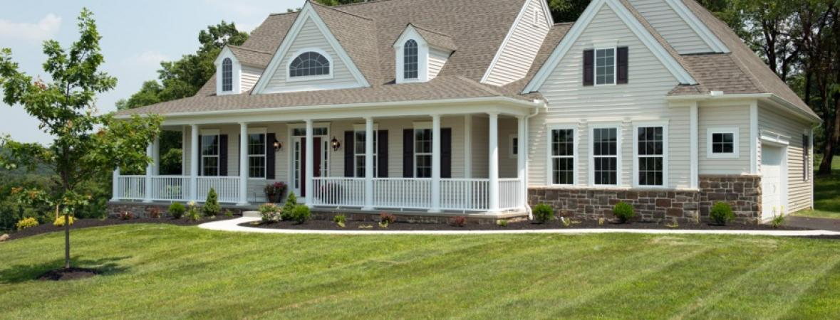 cream custom home with vinyl siding, stone veneer, large front porch, and attached garage