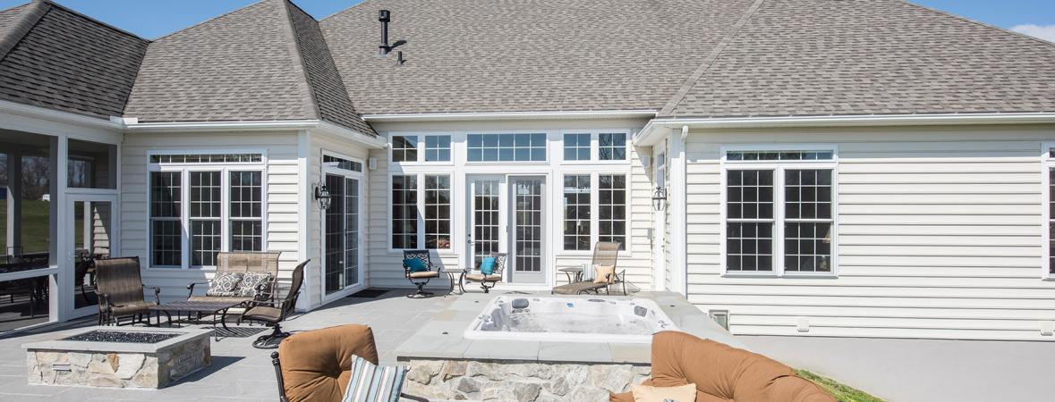 house with large outdoor patio including fire pit and hot tub