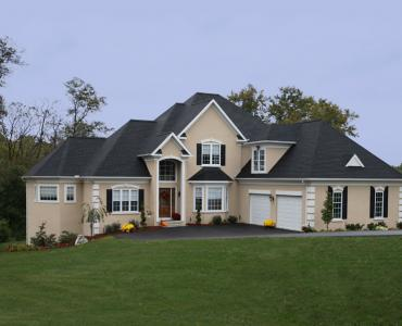 large tan custom home with attached two car garage
