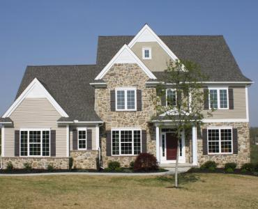 custom home with vinyl siding and stone veneer