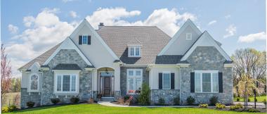 cream custom home with gray stone veneer