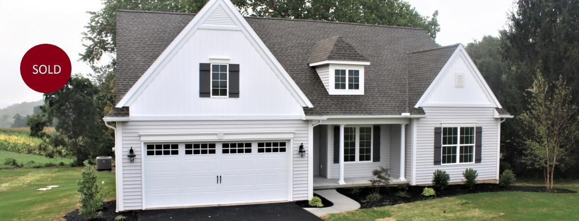exterior of custom home with off-white vinyl siding