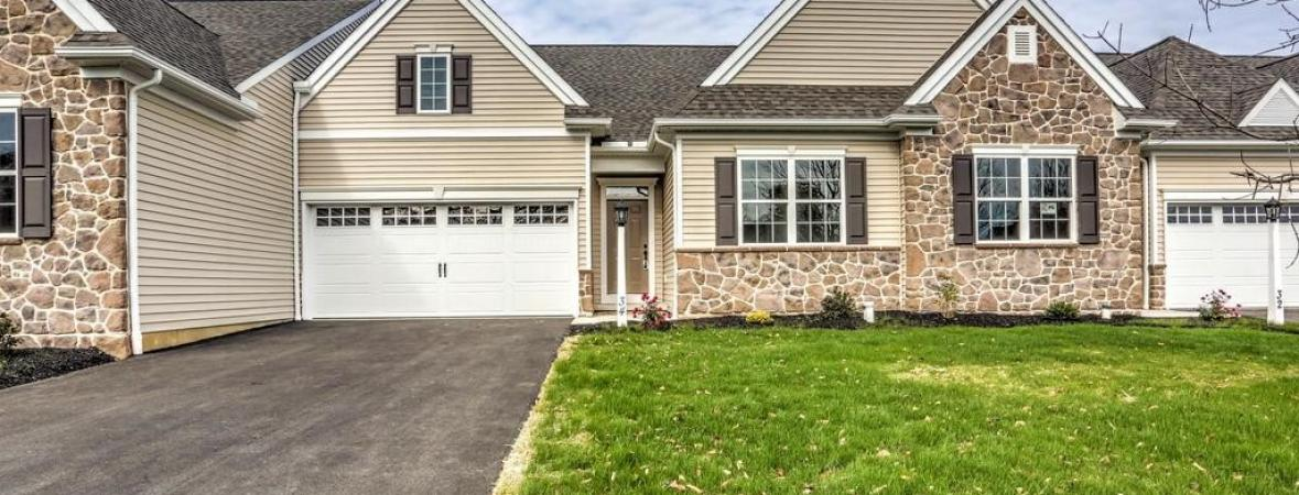 beige townhouse with stone veneer and attached garage