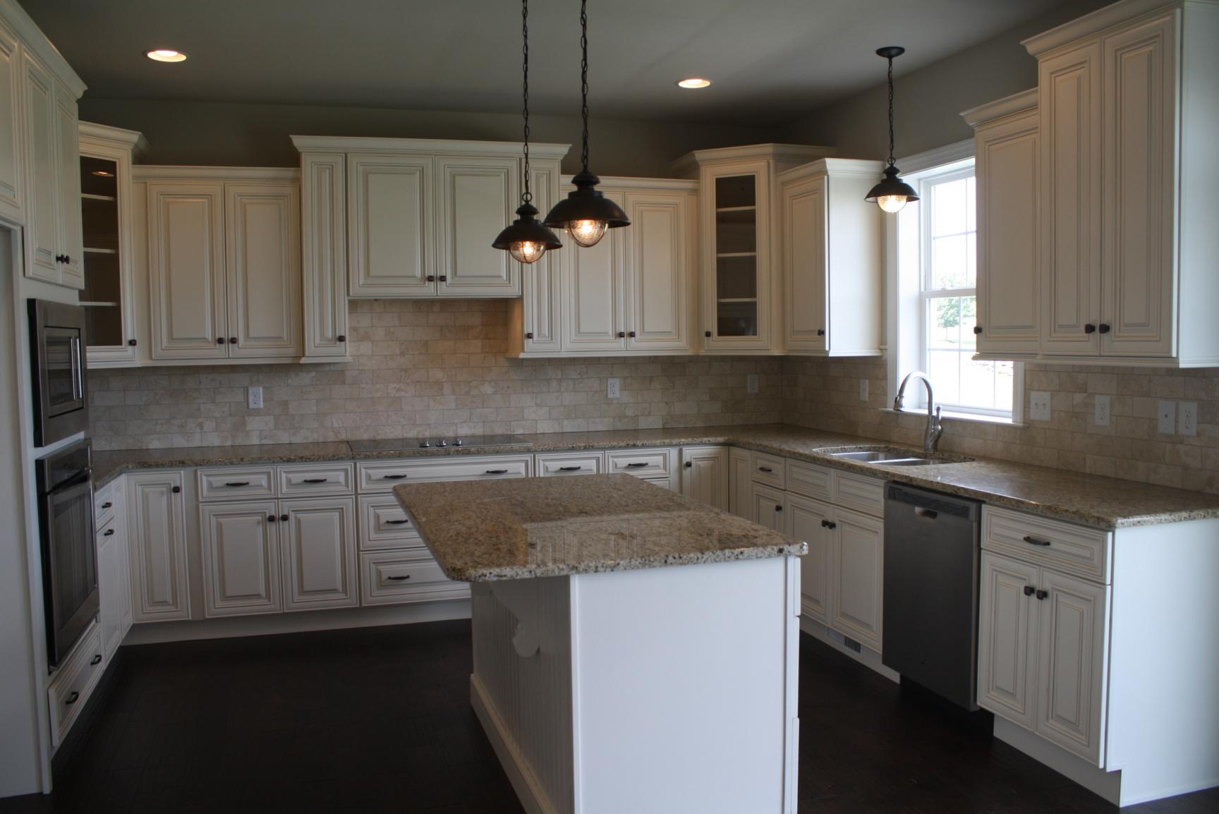 kitchen with white cabinets, tile backsplash, and island
