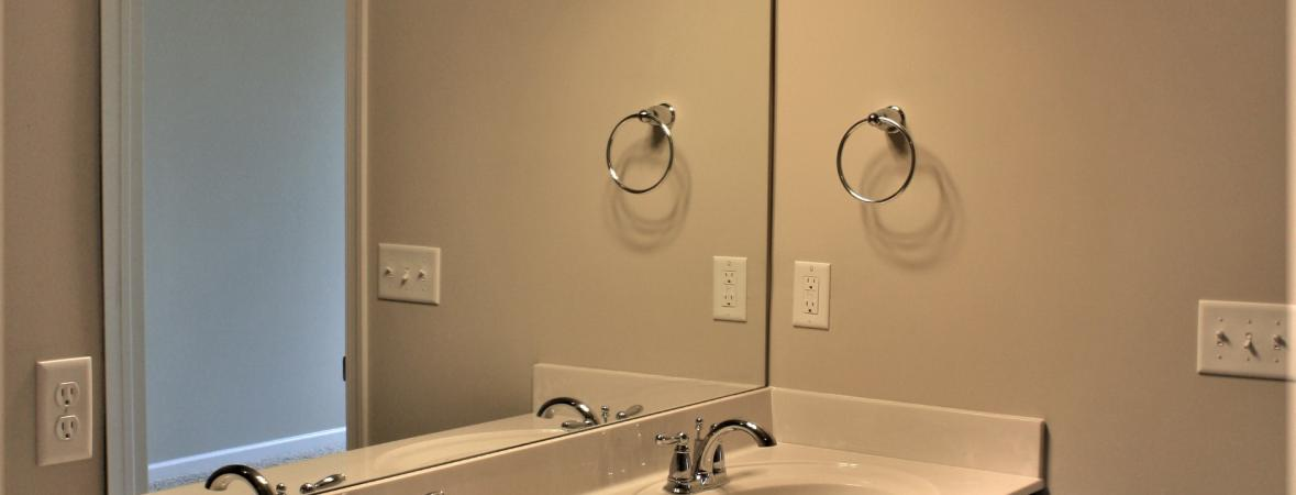 master bath with bright lights and double vanity