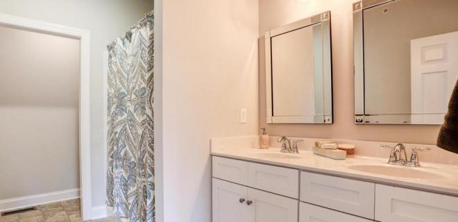 master bathroom with double vanity and walk-in shower unit