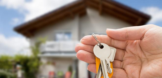 owning a home - closeup of hand with keys house in background