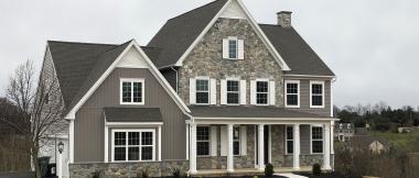 exterior of custom home with dark siding and stone siding