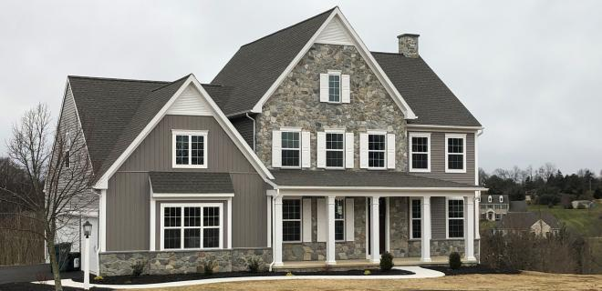 exterior of custom home with dark siding and stone siding