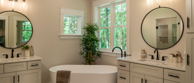 master bathroom with separate vanities and standalone tub